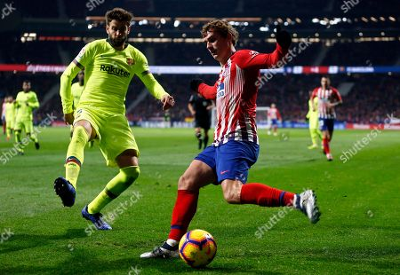 Xavi Hernandez. Barcelona's Gerard Pique, left, tries to block a shot from Atletico's Antoine Griezmann during a Spanish La Liga soccer match between Atletico Madrid and FC Barcelona at the Metropolitano stadium in Madrid