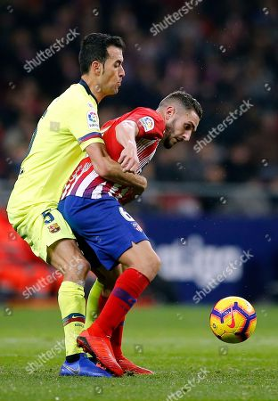 Xavi Hernandez. Barcelona's Sergio Busquets fights for the ball with Atletico's Koke, right, during a Spanish La Liga soccer match between Atletico Madrid and FC Barcelona at the Metropolitano stadium in Madrid