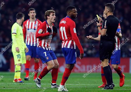 Xavi Hernandez. Referee Gil Manzano shows a yellow card to Atletico's Antoine Griezmann, left, during a Spanish La Liga soccer match between Atletico Madrid and FC Barcelona at the Metropolitano stadium in Madrid