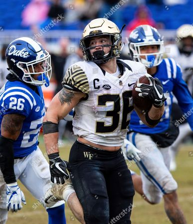 Wake Forest's Cade Carney (36) carries the ball ahead of Duke's Michael Carter II (26) and Jordan Hayes, right, during the second half of an NCAA college football game in Durham, N.C
