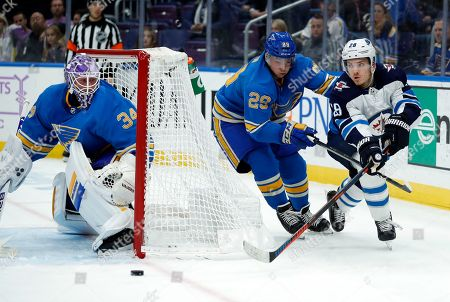 Winnipeg Jets' Jack Roslovic, right, passes around St. Louis Blues' Vince Dunn and goaltender Jake Allen, left, during the third period of an NHL hockey game, in St. Louis