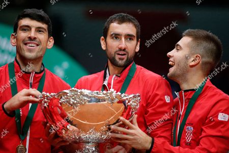 Croatia's Marin Cilic, center, holds the cup with teammates Borna Coric, right, and Franko Skugor after the team won the Davis Cup final between France and Croatia in Lille, northern France. Croatia claimed a second title in the team event following its maiden win in 2005