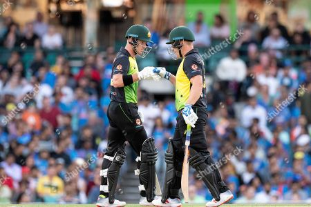 Australian player Aaron Finch (c) and Australian player D'Arcy Short touch gloves at the International Gillette T20 cricket match between Australia and India at The Sydney Cricket Ground in NSW