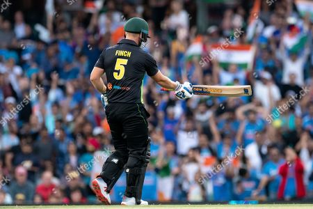 Australian player Aaron Finch (c) walks off after getting out at the International Gillette T20 cricket match between Australia and India at The Sydney Cricket Ground in NSW