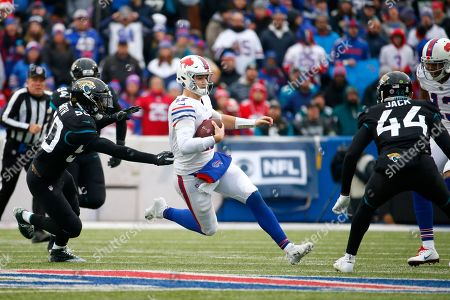 Buffalo Bills quarterback Josh Allen, center, slides after scrambling for yardage as Jacksonville Jaguars outside linebacker Telvin Smith (50) and middle linebacker Myles Jack (44) defend during the first half of an NFL football game, in Orchard Park, N.Y
