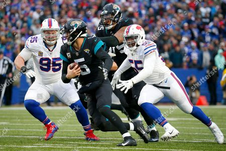 Jacksonville Jaguars quarterback Blake Bortles (5) tries to escape before being sacked by Buffalo Bills defensive tackle Kyle Williams (95) and defensive end Jerry Hughes (55) during the second half of an NFL football game, in Orchard Park, N.Y
