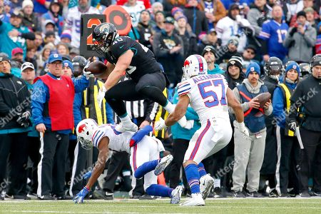 Stock Image of Jacksonville Jaguars fullback Tommy Bohanon, top, leaps over Buffalo Bills defensive back Levi Wallace, bottom, as Bills outside linebacker Lorenzo Alexander (57) looks on during the first half of an NFL football game, in Orchard Park, N.Y