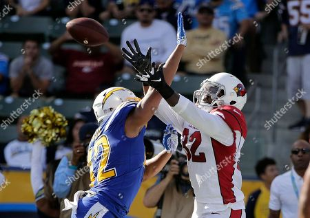 Stock Photo of Los Angeles Chargers linebacker Uchenna Nwosu, left, breaks up a pass intended for Arizona Cardinals fullback Derrick Coleman during the first half of an NFL football game, in Carson, Calif