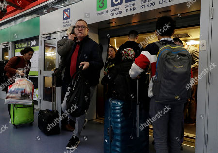 Travelers get off a airport train at O'Hare airport in Chicago, . More than 700 flights canceled as blizzard warning takes effect in Chicago. A winter storm warning has been extended for Cook, DuPage, Grundy, Kendall, Lake and Will counties through 9 a.m. Monday, according to the National Weather Service