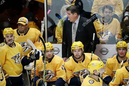 Nashville Predators head coach Peter Laviolette blows a bubble in the third period of an NHL hockey game between the Predators and the Anaheim Ducks, in Nashville, Tenn. The Predators won 5-2