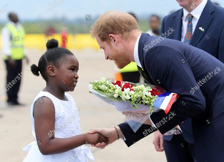 Britain's Prince Harry receives flowers from a girl upon his arrival at Kenneth Kaunda airport in Lusaka, . Prince Harry is on a State visit to Zambia at the request of the Commonwealth office and is expected to attend various events in the Southern African country