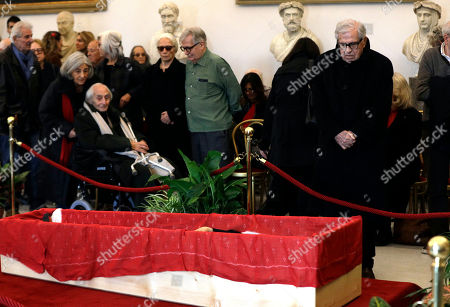 """Directors Paolo Taviani, right, and Citto Maselli, at left on a wheelchair, pay respect in front of the open coffin of Italian director Bernardo Bertolucci at Rome's Capitol Hill, . Bertolucci, who won Oscars with """"The Last Emperor"""" and whose erotic drama """"Last Tango in Paris"""" enthralled and shocked the world, has died Monday at the age of 77"""