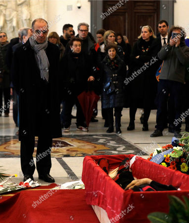 "Director Giuseppe Tornatore pays respect in front of the open coffin of Italian director Bernardo Bertolucci at Rome's Capitol Hill, . Bertolucci, who won Oscars with ""The Last Emperor"" and whose erotic drama ""Last Tango in Paris"" enthralled and shocked the world, has died Monday at the age of 77"
