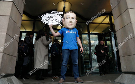 """An activist wearing a Facebook CEO Mark Zuckerberg mask stands in front of Portcullis House in Westminster as an international committee of parliamentarians met for a hearing on the impact of disinformation on democracy in London, . Lawmakers from nine countries grilled a Facebook executive who came in place of Zuckerberg on Tuesday as part of an international hearing at Britain's parliament on disinformation and """"fake news"""
