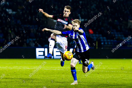Stock Image of Christian Doidge of Bolton Wanderers challenges Ashley Baker of Sheffield Wednesday