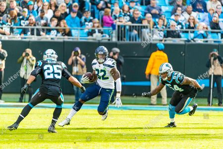Chris Carson, Eric Reid. Seattle Seahawks running back Chris Carson (32) in action against Carolina Panthers strong safety Eric Reid (25) and Carolina Panthers outside linebacker Shaq Green-Thompson (54) NFL football game between the Seattle Seahawks and the Carolina Panthers, in Charlotte, N.C