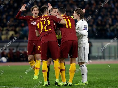 Roma forward Stephan El Shaarawy, left, and Aleksander Kolarov take on referee Clement Turpin as Real midfielder Luka Modric, right, looks at them, during a Champions League, Group G soccer match between Roma and Real Madrid at the Rome Olympic stadium