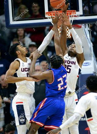 UConn's Tyler Polley (12) and Josh Carlton (25) defend against UMass-Lowell's Christian Lutete (23) during the first half of an NCAA college basketball game, in Storrs, Conn
