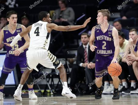 Western Carolina's Matt Halvorsen (2) drives against Wake Forest's Torry Johnson (4) during the second half of an NCAA college basketball game in Winston-Salem, N.C