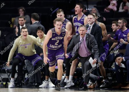 Western Carolina players react after Matt Halvorsen (2) makes a 3-point basket against Wake Forest during the second half of an NCAA college basketball game in Winston-Salem, N.C