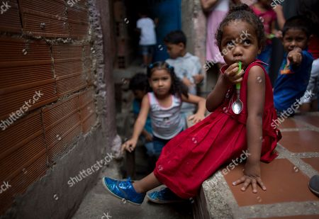 Stock Image of A girl holds her spoon as she waits to receive a meal at a children's center in the La Vega neighborhood of Caracas, Venezuela. Opposition activist Roberto Patino says that he's deferred his political ambitions to focus on feeding 1,800 children five days a week in 21 slums of Caracas
