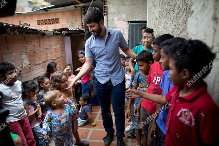 Roberto Patino greets children at a children's center in the La Vega neighborhood of Caracas, Venezuela. Patino, a rising star in Venezuela's unravelling opposition movement, and other grassroots organizers in their 20s and 30s have been feeding children, encouraging women to become community activists and organizing protests to demand public services like reliable drinking water and electricity