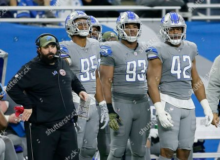 Stock Image of Detroit Lions head coach Matt Patricia watches from the bench with defensive end Romeo Okwara (95), defensive end Da'Shawn Hand (93) and outside linebacker Devon Kennard (42) during the second half of an NFL football game against the Carolina Panthers, in Detroit
